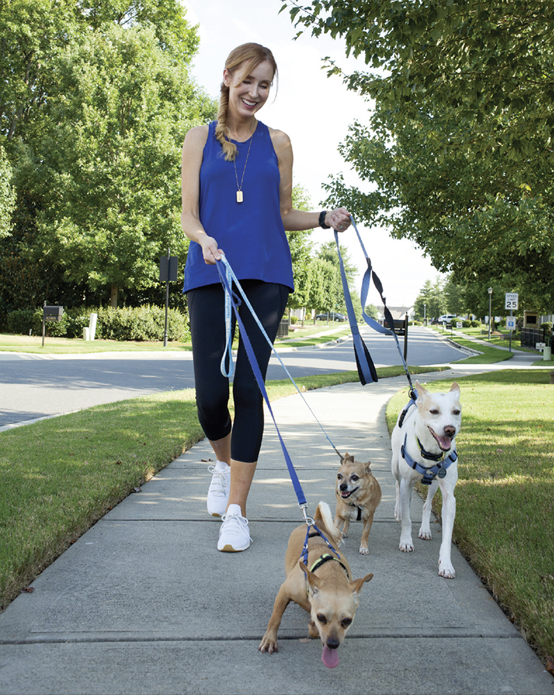 Happy woman walking three small dogs.